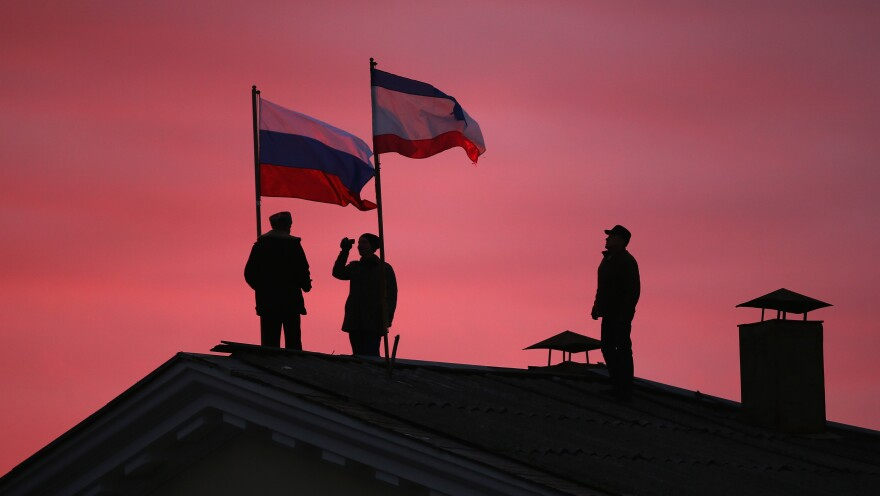 Men install a Russian flag and a Crimean flag Monday on the roof of the city hall building in the Crimean city of  Bakhchysarai. Crimeans voted overwhelmingly on Sunday to join with Russia. Ukraine's government rejects the move as illegitimate.