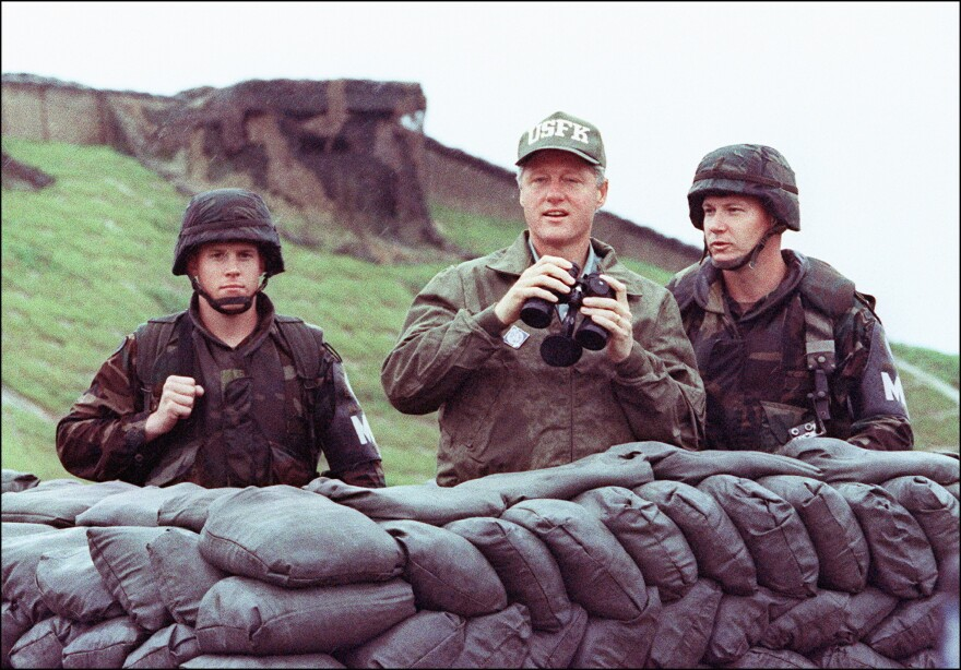 President Bill Clinton in a picture taken July 11, 1993, uses binoculars to look across the demilitarized zone into North Korea with two U.S. soldiers during his trip to South Korea.