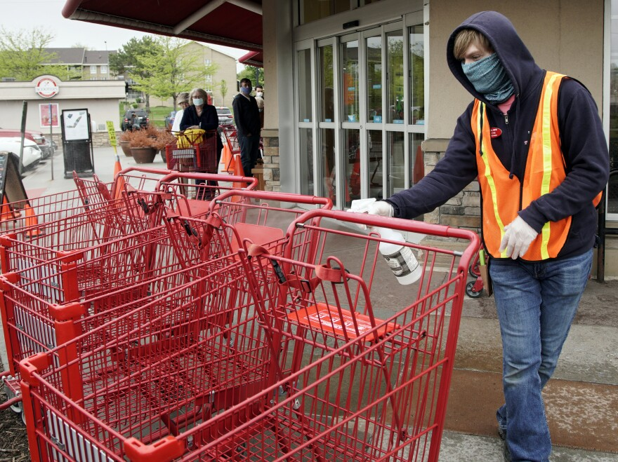 A Trader Joe's worker disinfects shopping carts and controls the number of customers allowed to shop at one time in Omaha, Neb., on May 7, 2020. Grocers like Trader Joe's are offering pay incentives to encourage their workers to get vaccinated against COVID-19.