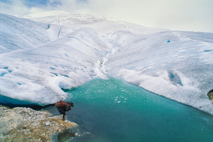 A barefoot porter totes a load for an expedition visiting one of the remaining glaciers near the equator, 16,000 feet high on the highest peak in Papua, Indonesia.