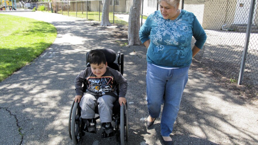 Teresa Soto watches as her son, Emmanuel Soto, 3, who was born with spina bifida, wheels himself over broken pavement on the path home from the playground near their house.