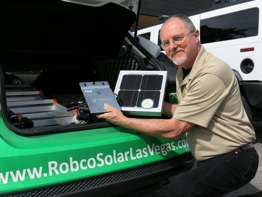 Robco Electric Sales and Marketing Manager Tim Webb shows off a solar panel from his sales kit. Since regulators have phased out solar incentives, his car often sits in the company parking lot.