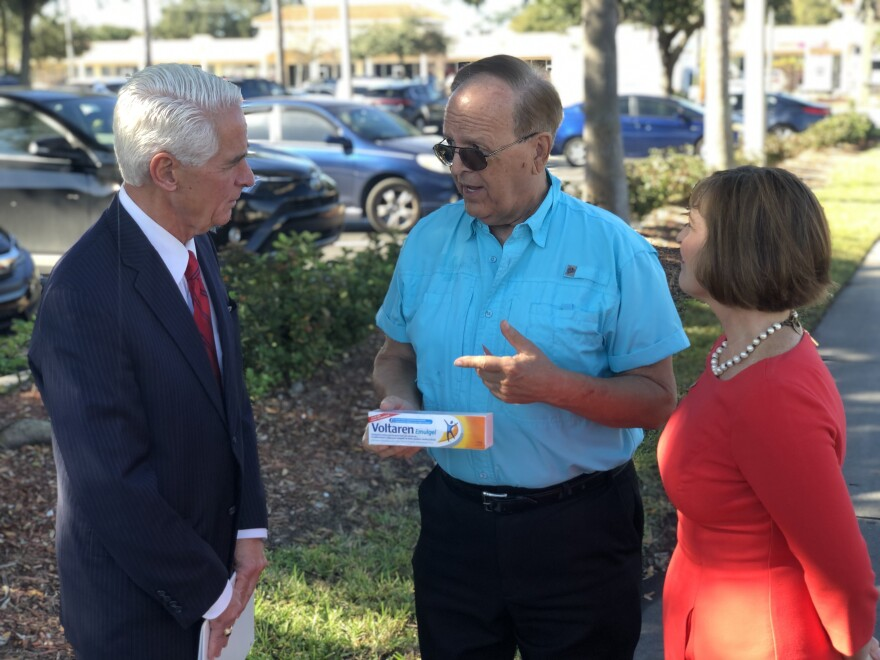 U.S. Representatives Charie Crist and Kathy Castor talk with older man in blue shirt holding joint pain salve box.