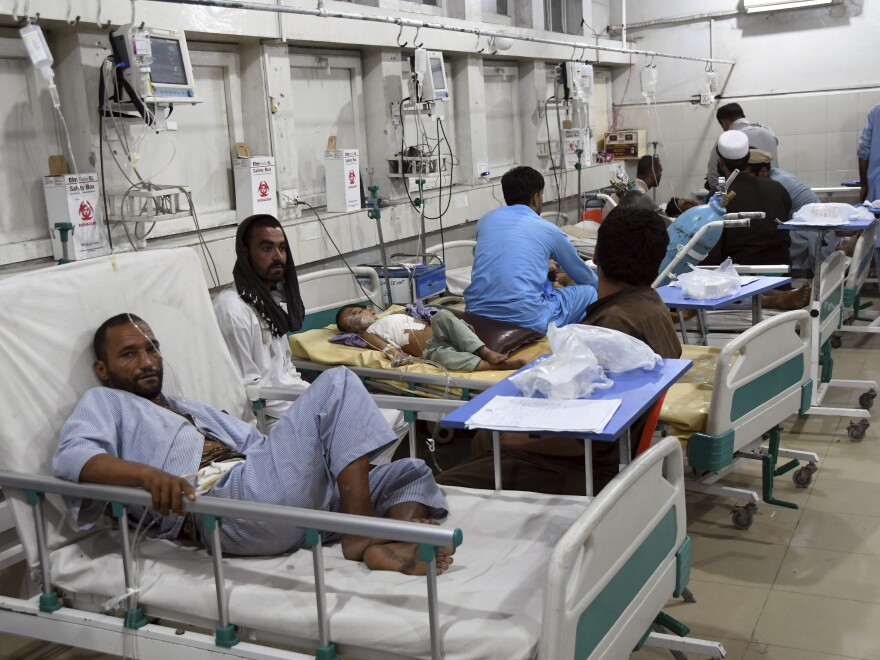Wounded Afghans lie on a bed at a hospital after a bomb attack in the city of Jalalabad, east of Kabul, on Saturday.