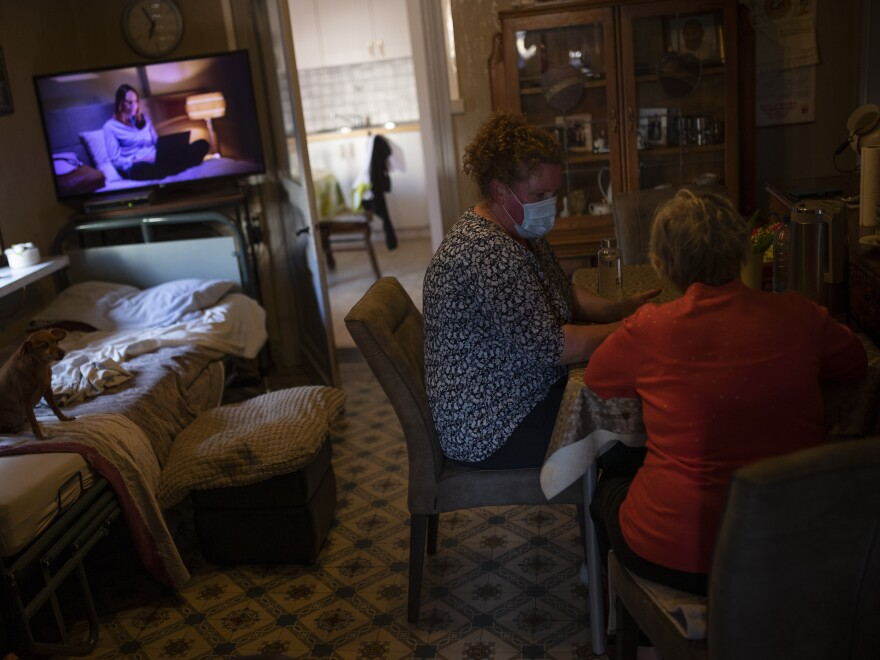 Home care worker Rosalinda De Pooter, wearing a face mask, plays a table game with her client Josephine Claes, 76, during a partial lockdown against the spread of COVID-19 in Booischot, Belgium on April 27, 2020.