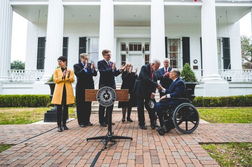 Texas Gov. Greg Abbott shakes hands with Jack Wilson, who was awarded the Governor's Medal of Courage after shooting a gunman at the West Freeway Church in White Settlement last month.
