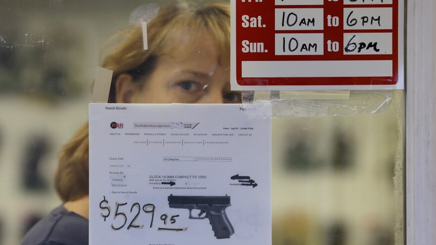 A clerk peers out from a gun shop in Seattle on Wednesday.