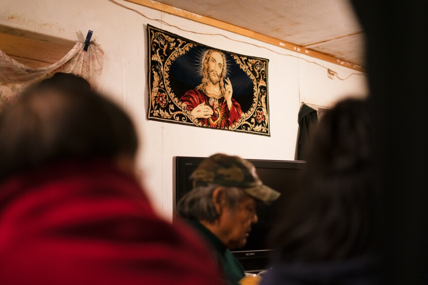 A tapestry depicting Jesus Christ hangs on the wall of a home where friends and family gather to mourn the death of a loved one in Toksook Bay in January.