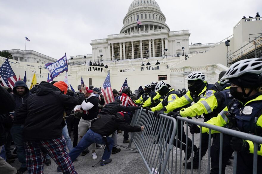 Rioters at the capitol try to push down a police barricade.