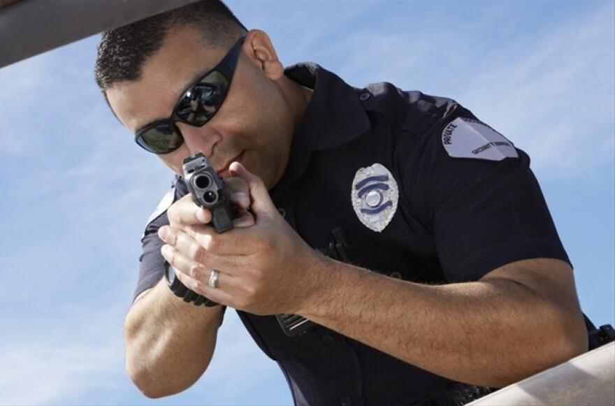 Police-Officer-Aiming-Gun-At-Broken-Car-Shutterstock-800x430.jpg