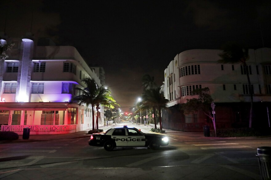 A police car patrols through the usual bustling South Beach ahead of Hurricane Irma in Miami Beach, Fla., Friday, Sept. 8, 2017. Florida asked 5.6 million people to evacuate ahead of Hurricane Irma, or more than one quarter of the state's population. A bill passed by the Florida Senate this week would require cities and counties to report evacuation orders, emergency shelter openings and a list of other emergency situations to the state. Reporting is not currently mandatory under state law.