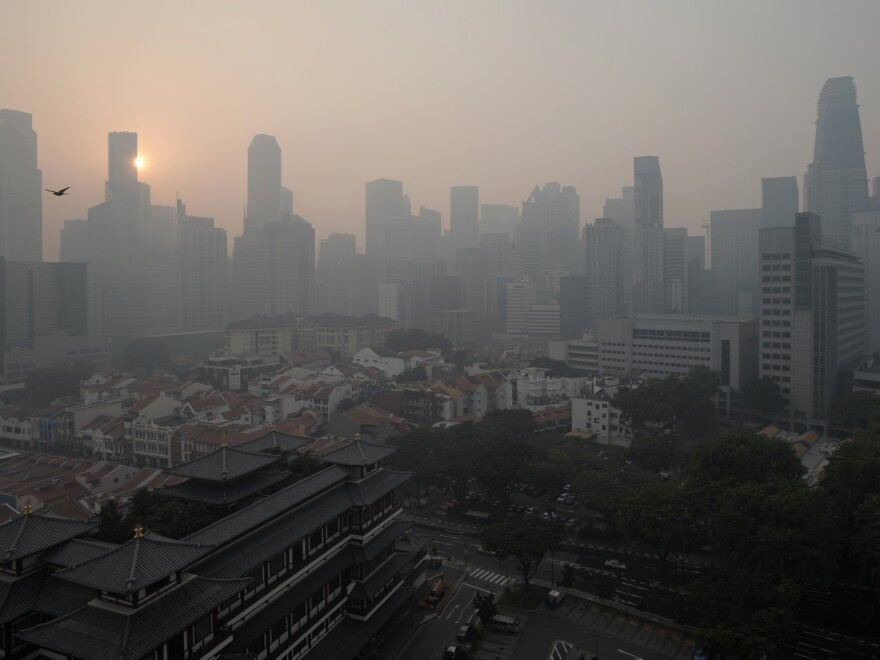 The sun rises over the Singapore Central Business District as smog shrouds the city-state on Thursday.
