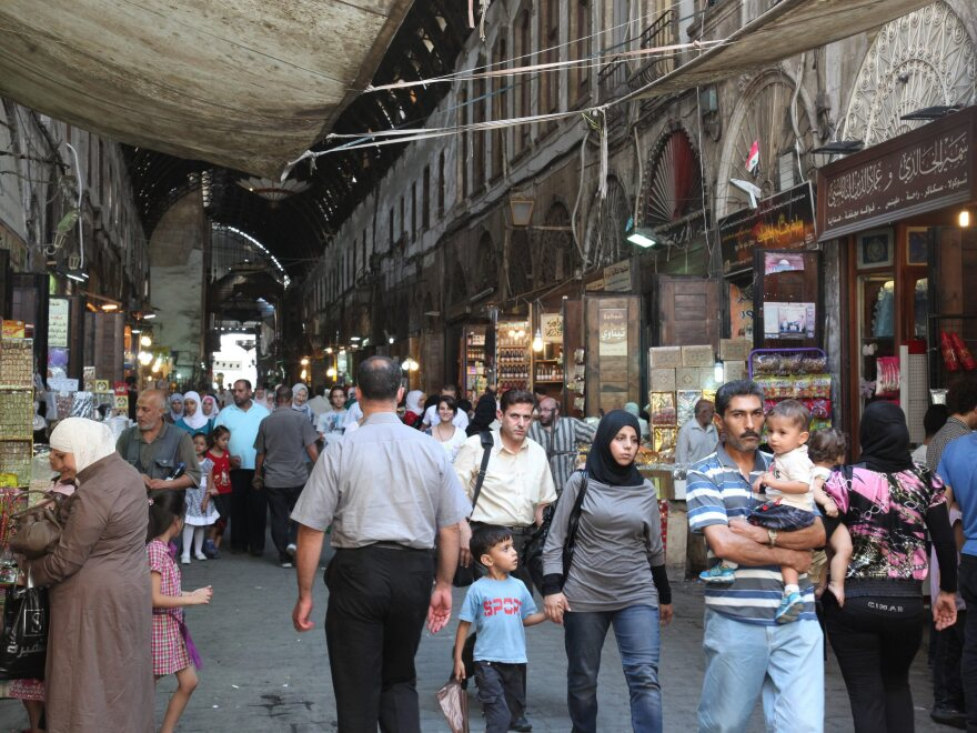 Syrians walk at the al-Bzoureya market in Old Damascus on Thursday.