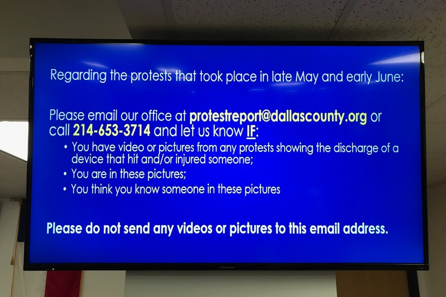 A television monitor displays a message from the Dallas District Attorney on a blue background asking for people to contact the office if they have photos or video of police using weapons that injured protestors in late May and early June.
