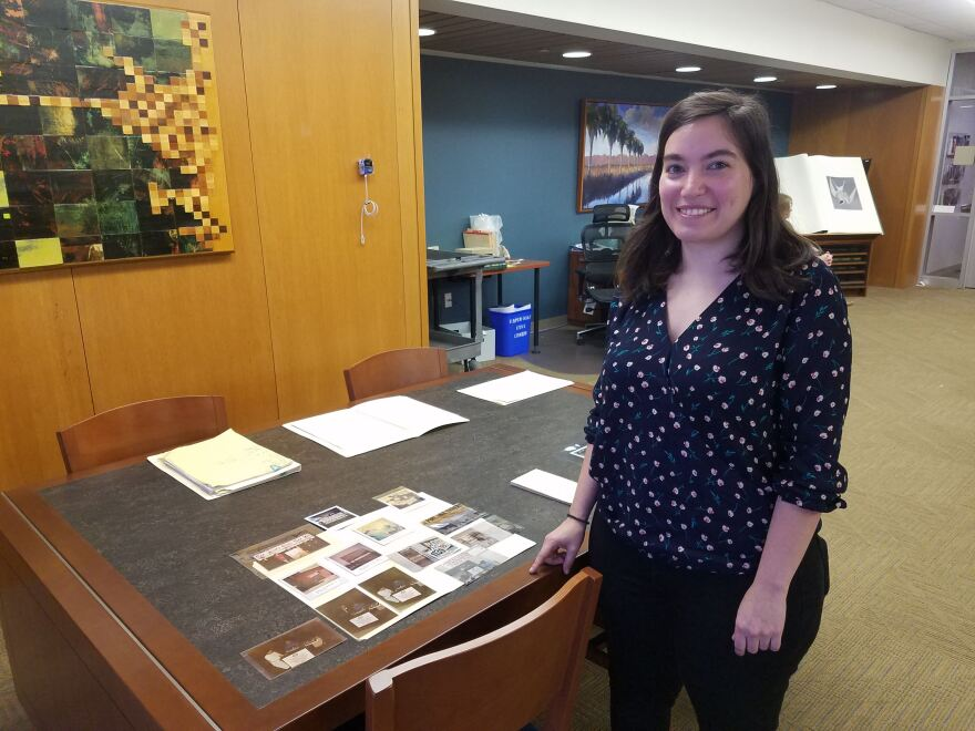 Moira Mackay stands next to some of photos archived in the SVREP special collection at UTSA.