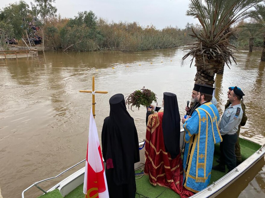 Orthodox Church Patriarch of Jerusalem Theophilos III tosses a bouquet of basil into the Jordan River, at Qasr al-Yahud, a baptism site near the West Bank city of Jericho, on Jan. 18. Basil is believed to have grown near the cross where Jesus was crucified and is used for blessings.
