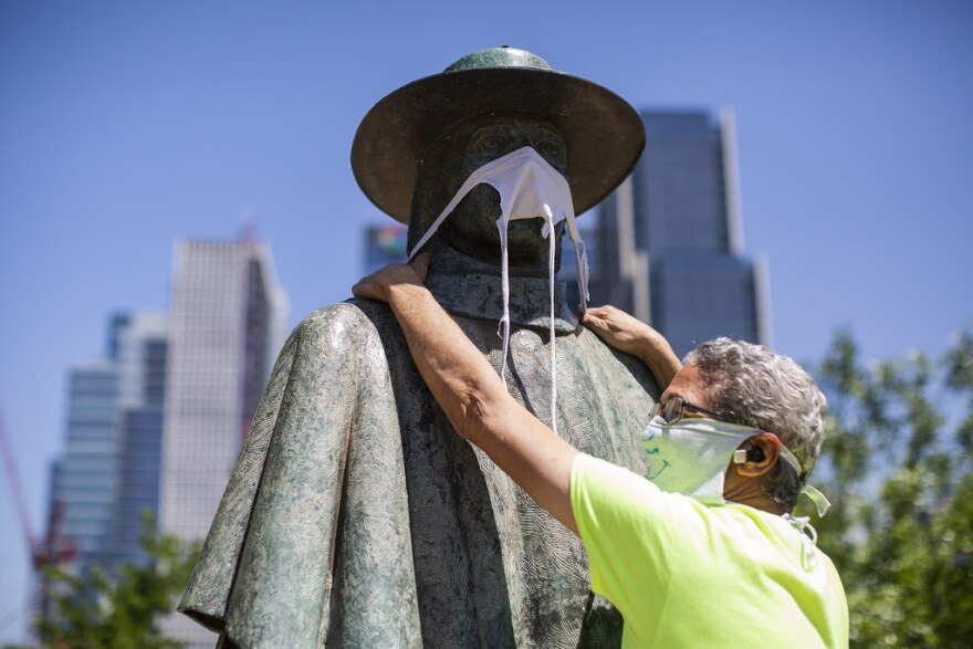 Jeff Levine puts a face mask over the statute of Stevie Ray Vaughn at Auditorium Shores on April 16.