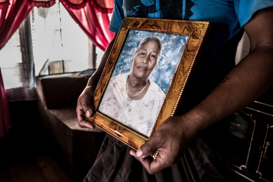 Mesak holds a picture of his mother, Alfrida, who died in 2012.