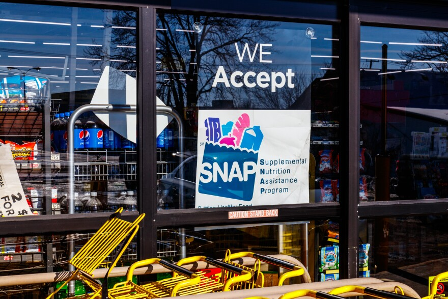 Photo of a SNAP sign in a grocery story window.