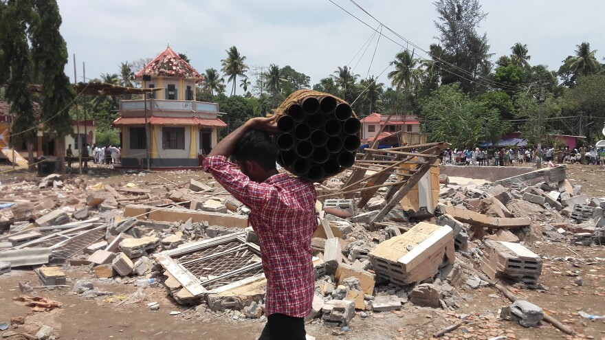 A man carries empty fireworks shells past a collapsed building after a massive fire broke out during a fireworks display at a temple complex in Paravoor village in the state of Kerala, India.