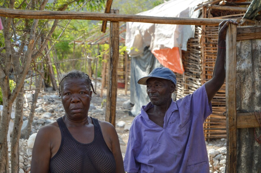 "Charlesina Lyone and her husband stand in the shell of their house in Tete de l'Eau, Haiti. They're living off their meager savings: ""If we have one pot of rice, we'll separate it in two. We'll make it last twice as long."""