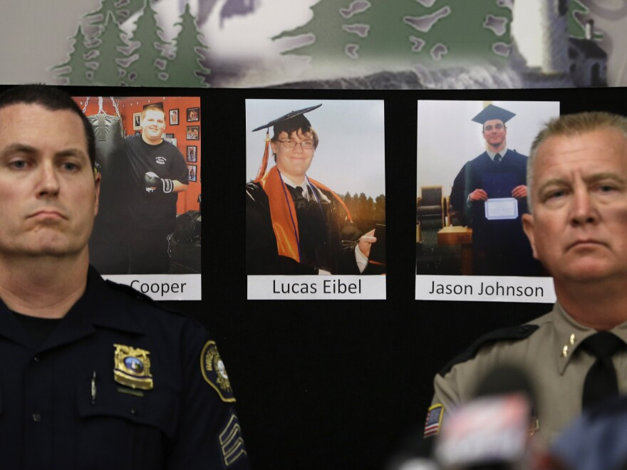 Photos of victims of the mass shooting at Umpqua Community College in Roseburg, Ore., are displayed behind Portland Police Sgt. Peter Simpson (left) and Douglas County Sheriff John Hanlin.