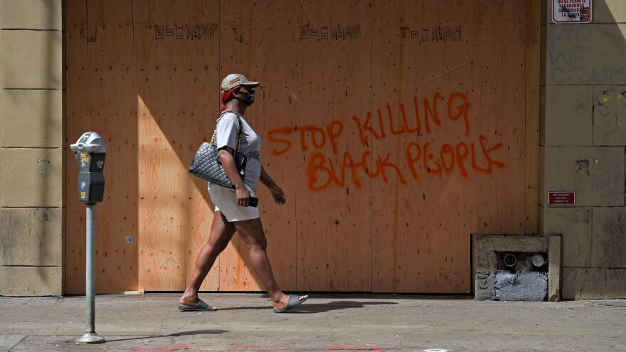 A woman walks past a boarded up store in downtown Los Angeles on Sunday. Professor Jody David Armour says protesters today are more diverse and have more empathy than in 1992.