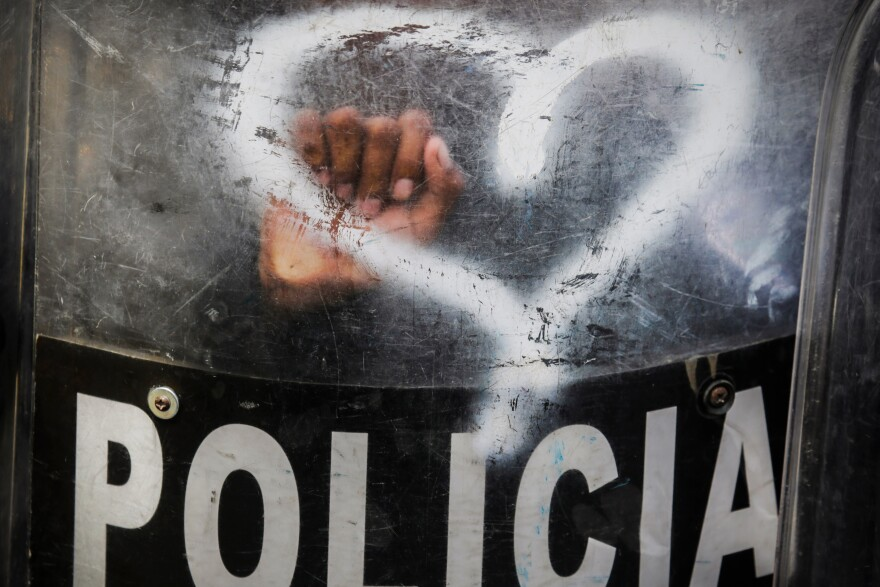 With heart-shaped graffiti spray-painted by activists on a shield, Nicaraguan riot police stand by in August 2019 as anti-government protesters in Managua call for the reinstatement of health workers who lost their jobs for assisting protesters during a deadly 2018 uprising against President Daniel Ortega.