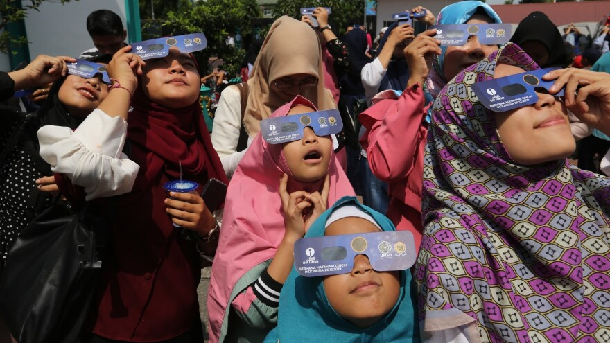 "Children witness the ""ring of fire"" solar eclipse using special glasses in Medan, North Sumatra, in Indonesia on Thursday."