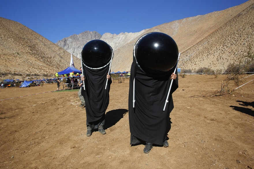 Observers in Paiguano, Chile, watch the sky while donning special suits prior to the total solar eclipse.