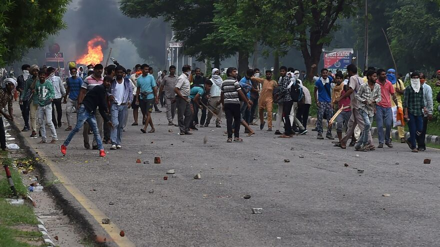 Some of the tens of thousands of Gurmeet Ram Rahim Singh's followers who gathered this week in Panchkula in Haryana state are seen throwing stones at security forces during clashes after the controversial guru was convicted of rape.
