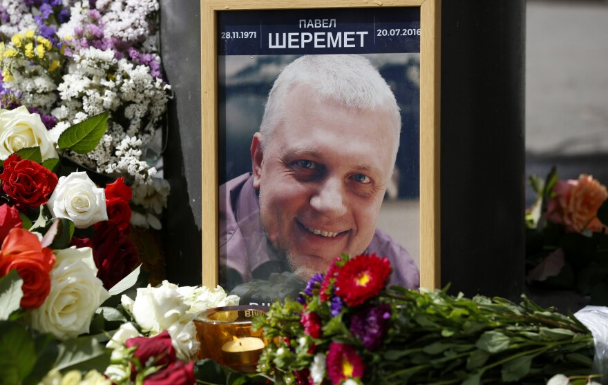 A portrait of journalist Pavel Sheremet is surrounded with flowers and candles near where he was killed.