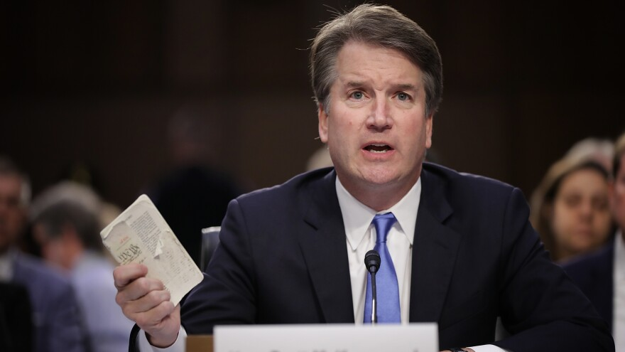 Supreme Court nominee Judge Brett Kavanaugh holds up a small copy of the U.S. Constitution while answering questions before the Senate Judiciary Committee during his confirmation hearing Wednesday on Capitol Hill.