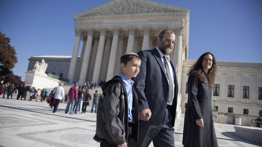 Ari Zivotofsky (center) walks with then 9-year-old son Menachem, outside the Supreme Court in Washington on Nov. 7, 2011. Their case, regarding the desire to have their son's U.S. passport list his place of birth as Israel, returns to the Supreme Court this Monday.