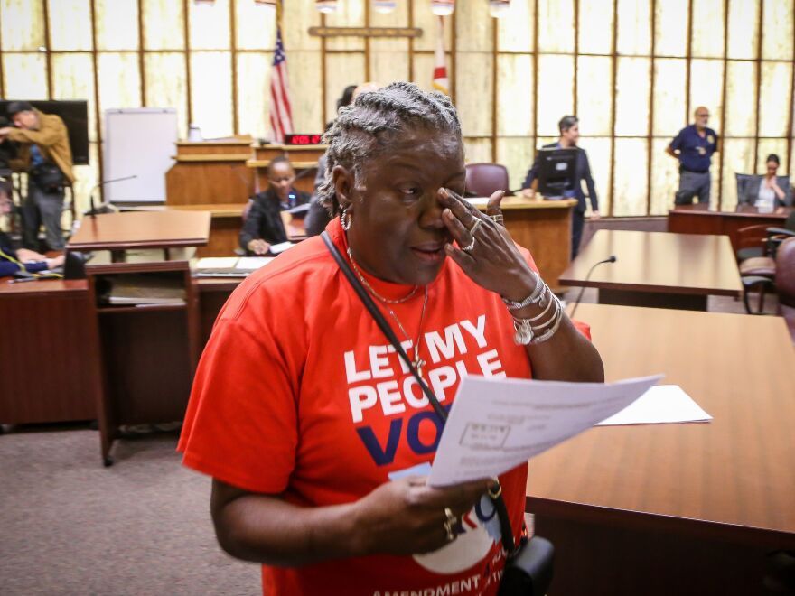 Carmen Brown weeps as she walks away holding a paper restoring her right to vote during a special court hearing aimed at restoring that right in a Miami-Dade County courtroom on Nov. 8, 2019. A federal lawsuit currently underway would make it easier for others to get their voting rights restored by eliminating requirements that they pay fines and fees.