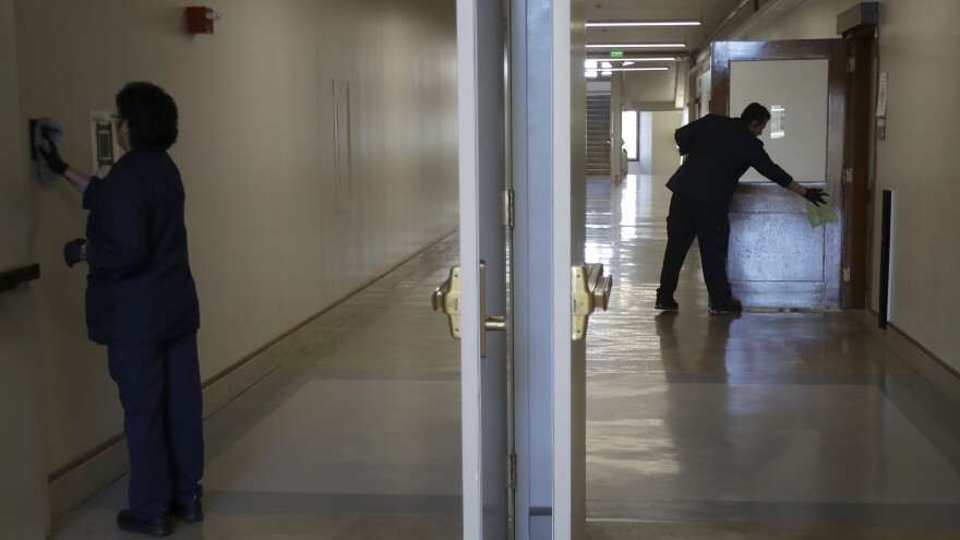 Janitors clean in a hallway in Wheeler Hall on the University of California campus in Berkeley, Calif., on March 11.