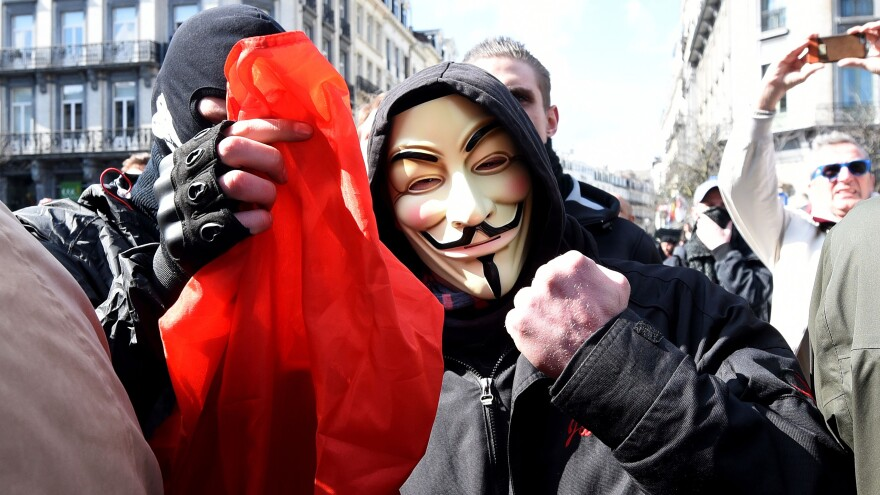 A masked man raises a fist and the Belgian flag outside the stock exchange in Brussels on Sunday, at a square filled with memorials to the victims of Tuesday's terrorist attacks. Tensions mounted after the square, occupied by mourners, was invaded by far-right protesters whom AFP identified as football hooligans.