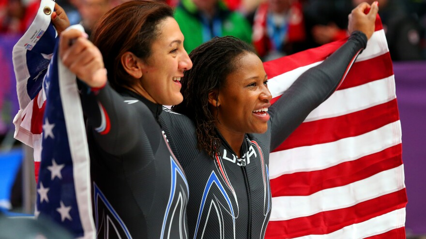 U.S. silver medalists Elana Meyers, left, and Lauryn Williams pose after their final run in the women's bobsled Wednesday. Williams becomes only the second American in history to win medals in both the Summer and Winter Olympics.