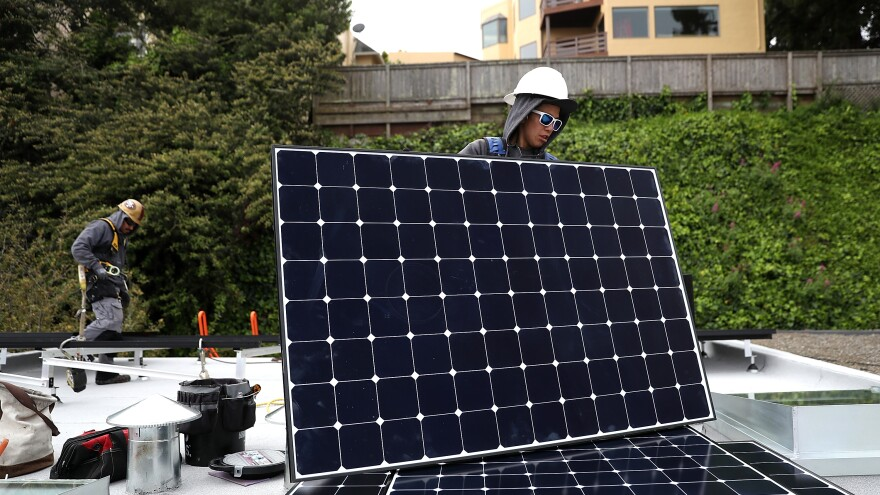 Luminalt solar installers Pam Quan (right) and Walter Morales (left) install solar panels on a roof in San Francisco on Wednesday. The California Energy Commission approved a regulation that would require all new homes in the state to have solar panels.