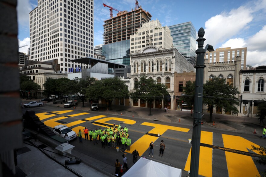 "Artists paint ""Black Austin Matters"" on a portion of Congress Avenue on Tuesday."