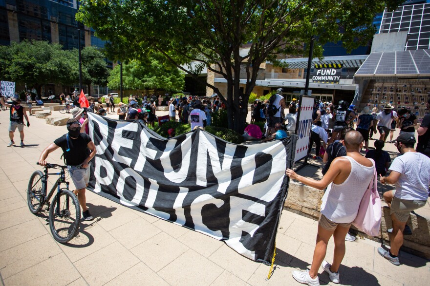 Protesters outside Austin City Hall on July 11 call for defunding the police department.