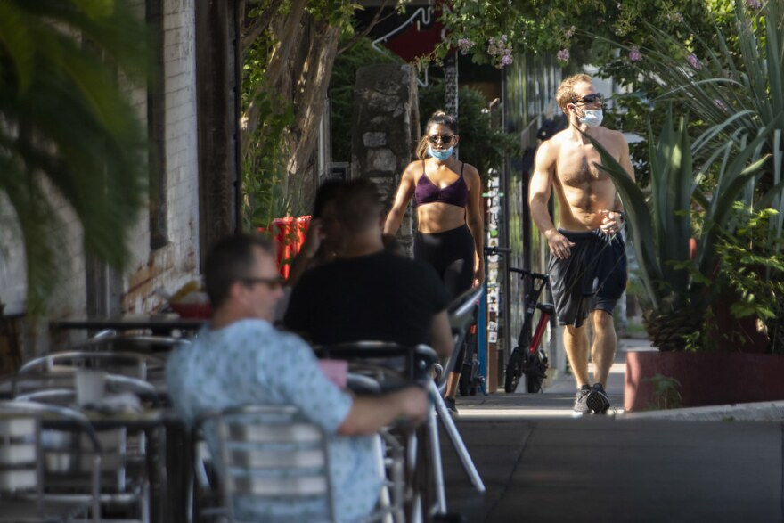 People walk along South Congress Avenue wearing masks on Wednesday.