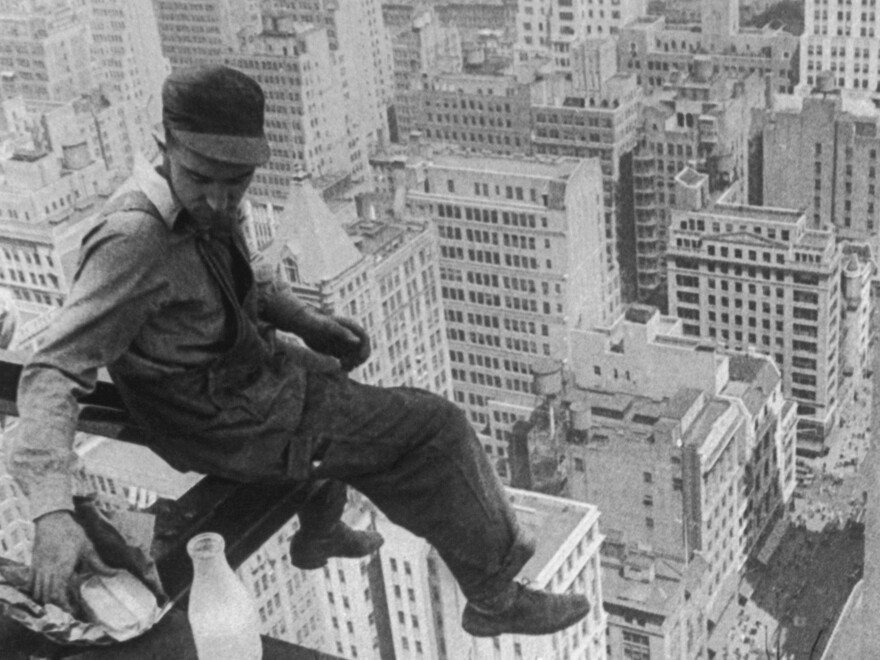 A worker pauses for a sandwich circa 1930, resting on a girder during the construction of a skyscraper.