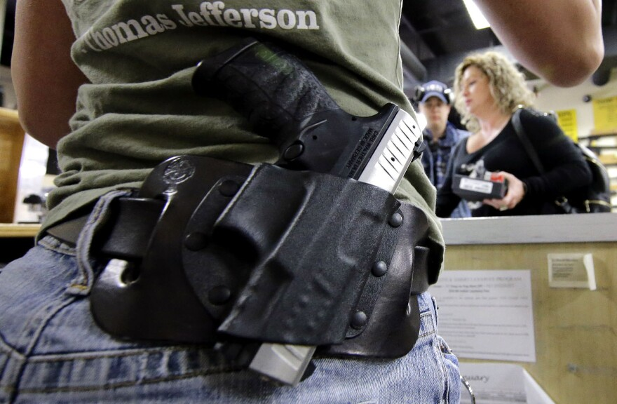 A gun store employee in Spring, Texas, carries a gun on her hip while working the counter in 2016.