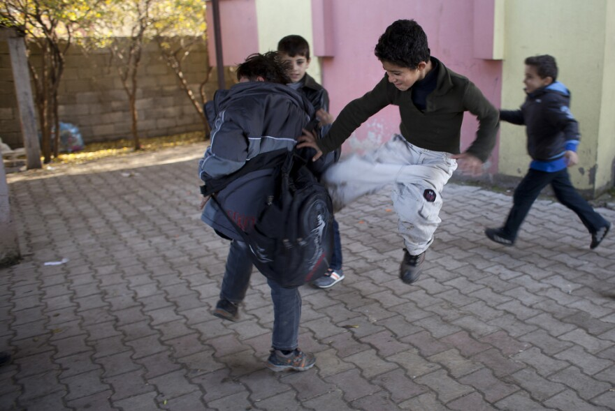 Some Syrian children play at wrestling and fighting during recess at the Albashayer School for Syrian Refugee Children. This type of play can be common among children who have witnessed traumatic events.