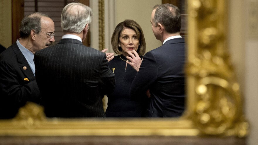 House Speaker Nancy Pelosi speaks with House Intelligence Committee Chairman Adam Schiff (right), House Foreign Affairs Committee Chairman Eliot Engel (left) and House Ways and Means Committee Chairman Richard Neal after the House voted to impeach President Trump on Dec. 18.