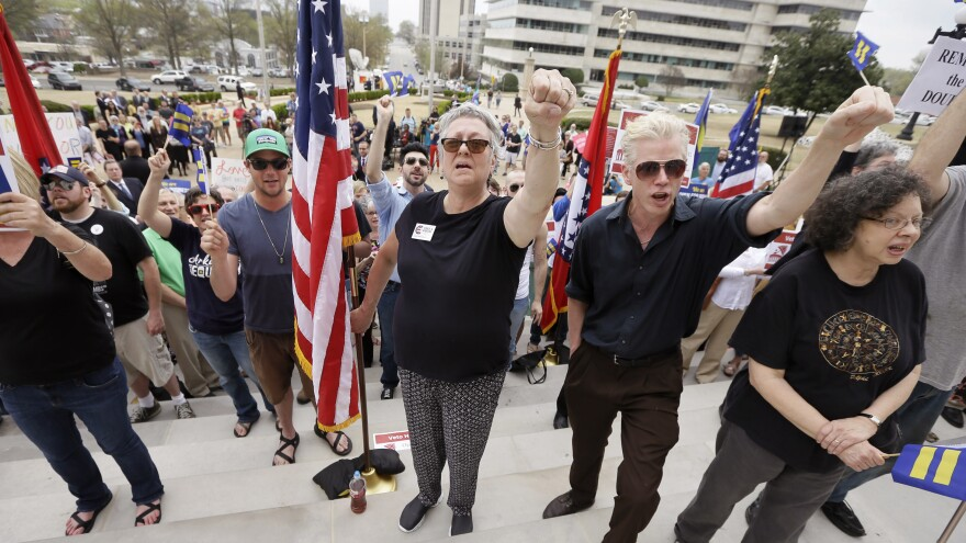 Opponents of an Arkansas religious objection measure chant outside the Arkansas state Capitol on Wednesday.