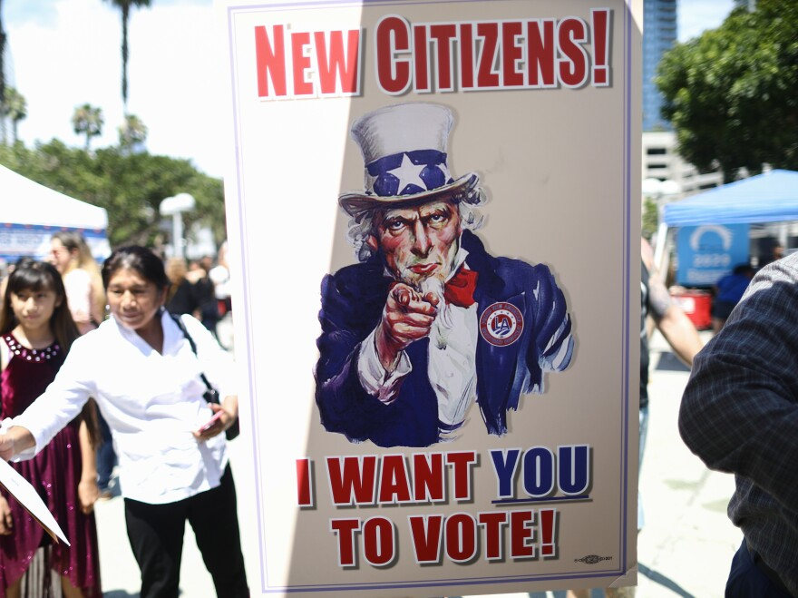 A sign encourages newly sworn-in U.S. citizens to register to vote outside a naturalization ceremony in 2019 in Los Angeles. After failing to get the now-blocked citizenship question on the 2020 census, the Trump administration is continuing to gather government records to produce citizenship data for redistricting.