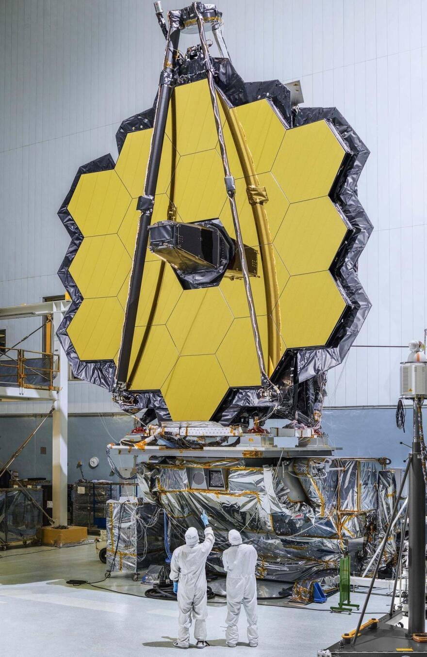 Technicians view the primary mirror for the James Webb Space Telescope. The thin gold coating on its mirror segments improves the reflection of infrared light.