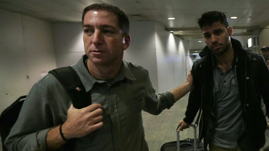 """Glenn Greenwald, left, and David Miranda after Miranda's arrival at Rio de Janeiro's International Airport on Aug. 19, 2013. Miranda had been detained for nine hours at London's Heathrow Airport. Authorities questioned him about Greenwald's reporting of the """"NSA leaks."""""""
